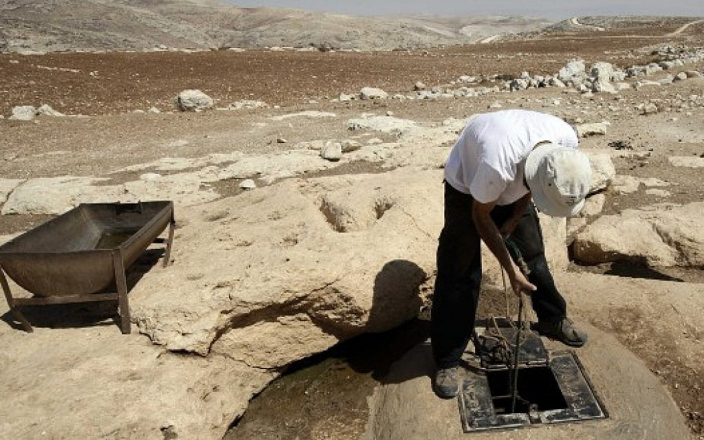 A man draws water from a well in the West Bank (photo credit: Abir Sultan/Flash90)