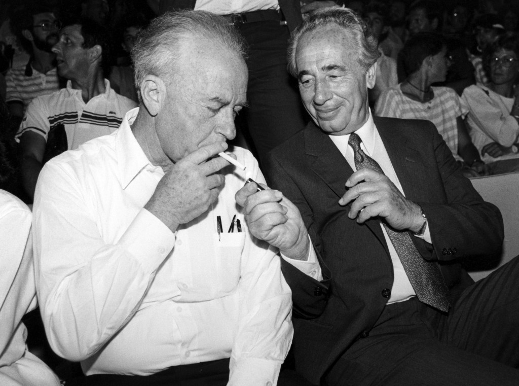 Shimon Peres lights the cigarette of Yitzhak Rabin, September 16, 1986. Photo by Moshe Shai/Flash90)