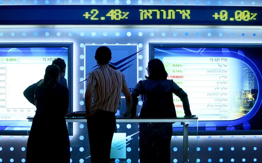 Illustrative: People watch a board showing price fluctuations at the Tel Aviv stock exchange. (Moshe Shai/FLASH90)
