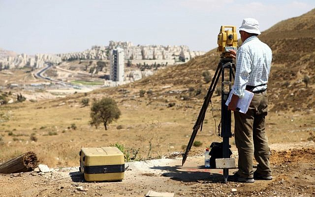 An engineer surveying the East Jerusalem neighborhood of Har Homa in 2012. (photo credit: Abir Sultan/Flash90)