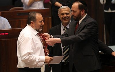 Shas minister Ariel Atias arranges Avigdor Liberman's tie at the Knesset, July 2010 (photo credit: Yossi Zamir/Flash90)