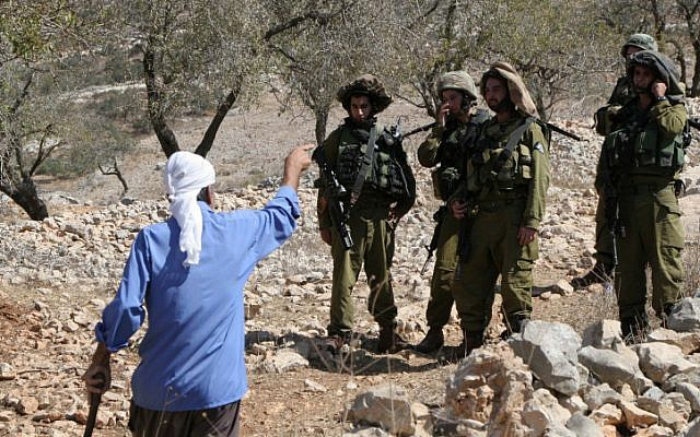 Israeli soldiers confront a Palestinian near the settlement of Yitzhar in September 2010 (photo credit: Wagdi Ashtiyeh/Flash90)
