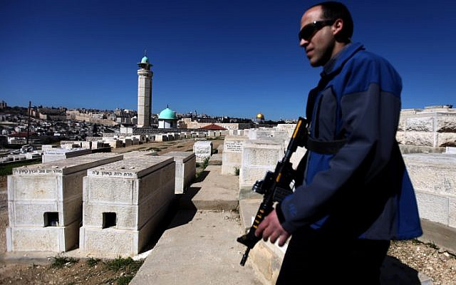 A security guard patrols the Mount of Olives in Jerusalem during a ministerial visit. (photo credit: Abir Sultan/Flash90)
