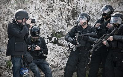 A photojournalist takes a photo of riot policemen during clashes in east Jerusalem in February of 2011. (Illustrative photo: Ruben Salvadori/Flash 90)