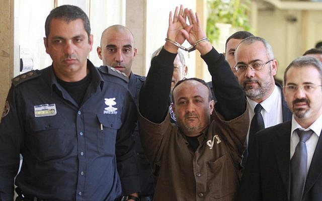 Palestinian Fatah leader Marwan Barghouti is escorted by Israeli police into Jerusalem's Magistrate Court to testify as part of a US civil lawsuit against the Palestinian leadership, in January 2012. (photo credit: Flash90)