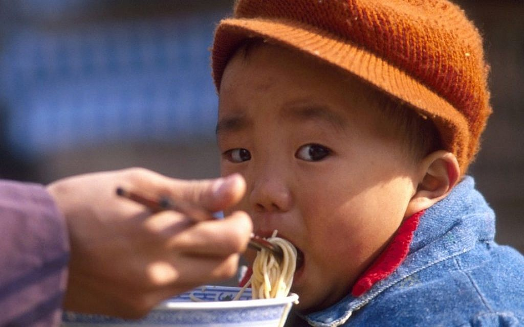Illustrative: A Chinese boy eats noodles in Beijing. (Serge Attal/Flash90)