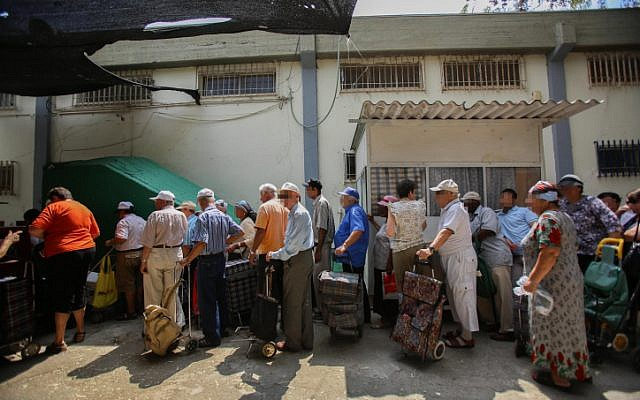 People waiting in line for food packages at a distribution center for needy in Lod on September 11, 2012.  (photo credit: Yonatan Sindel/Flash90)