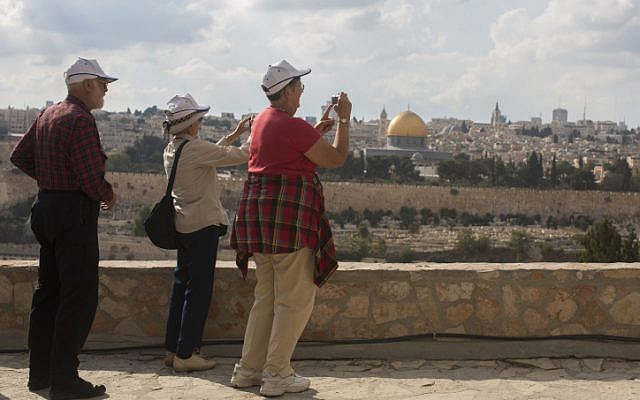 Tourists take pictures from the Mount of Olives, overlooking the walls of the Old City of Jerusalem and its distinctive golden Dome of the Rock. (photo credit: Yonatan Sindel/Flash90)