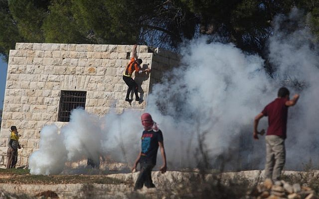 A Palestinian protester hurls stones at Israeli soldiers during a protest against settlement activity in the West Bank village of Nabi Saleh near Ramallah, Friday, November 30, 2012 (photo credit: Issam Rimawi/Flash90)