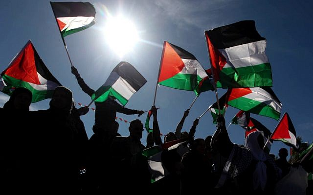 Palestinians wave their national flag during a rally marking the UN General Assembly's upgrading of the Palestinians' status in Ramallah, on Sunday, December 2. (photo credit: Issam Rimawi/Flash90)