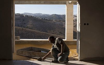 A Palestinian man working in construction in the settlement of Ma'aleh Adumim, near the E1 tract. (photo credit: Yonatan Sindel/Flash90)