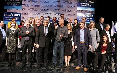Yesh Atid Chairman Yair Lapid, center with tie, surrounded by his fellow party members after announcing their list for the upcoming Knesset elections in early December, 2012. Most of his list comprises new MKs, 19 of whom are entering the next Knesset. (photo credit: Yehoshua Yosef/Flash90)