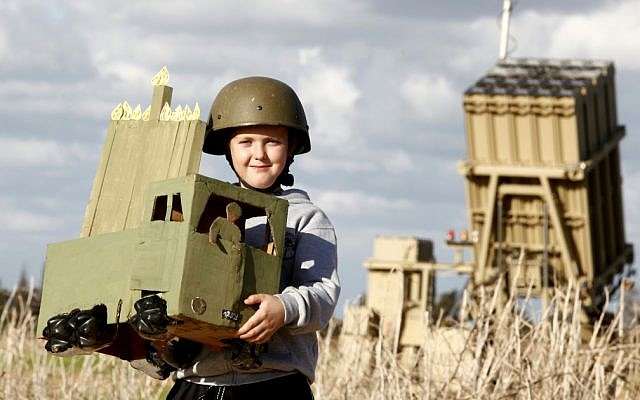 A child in Ashkelon holds a homemade Menorah in front of the Iron Dome unit stationed in the city.  The holiday of Hanukkah begins Saturday night (photo credit: Edi Israel/FLASH90)
