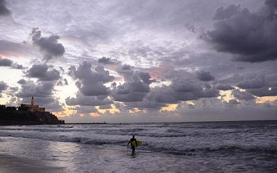 A lone surfer walks along the stormy shoreline of Tel-Aviv (photo credit: Tomer Neuberg/Flash90)