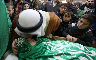 Palestinians bear the corpse of Mohammed Salayme during his funeral procession on December 13 in the West Bank city of Hebron. Israeli police said Salayme was shot after threatening border policeman in the city with a weapon, which turned out to be a toy. (photo credit: Issam Rimawi/Flash90)