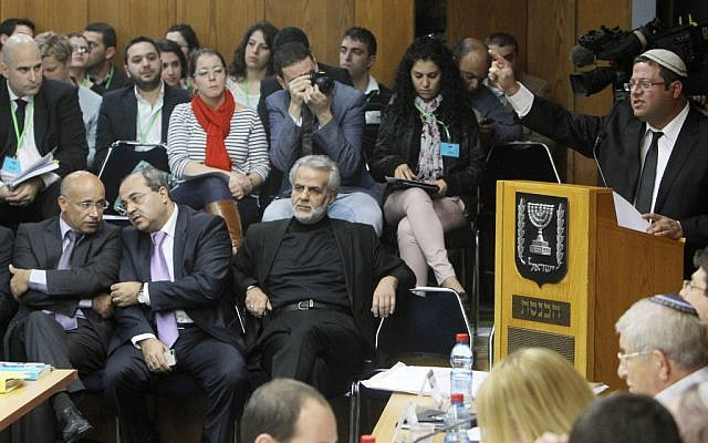 Would-be MK Itamar Ben Gvir, a far-right candidate whose Otzma Leyisrael party has been accused of racism, speaks at a Knesset Election Committee meeting where a vote was passed banning Arab parliament member Hanin Zoabi from running in the upcoming elections. Arab MKs including Ahmed Tibi (front, second from left) look on. (photo credit: Miriam Alster/Flash90)