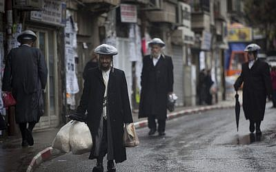 Ultra Orthodox men walk the streets of Jerusalem in the rain on Friday, December 21 (photo credit: Yonatan Sindel/Flash90)