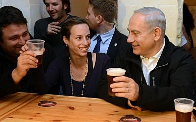 Feeling good about the elections, Prime Minister Benjamin Netanyahu has a drink with students in Beersheba (photo credit: Kobi Gideon/GPO/Flash90)