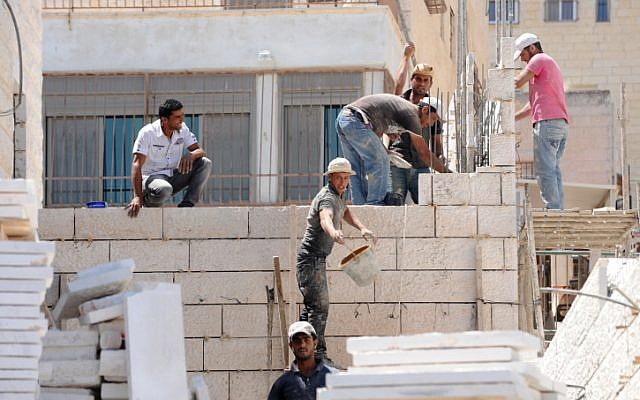 An illustrative photo of workers building a home in East Jerusalem's Ramat Shlomo neighborhood, June 2011. (photo credit: Gili Yaari/Flash90)