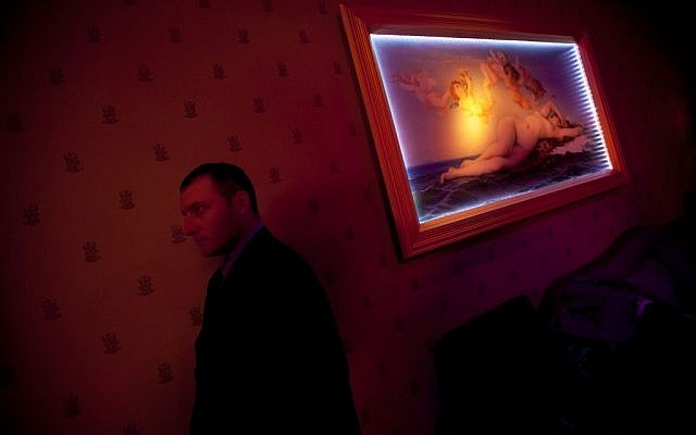 A Russian-speaking Israeli security guard works the VIP room of the Russian Soho nightclub in Tel Aviv. (photo credit: AP Photo/Oded Balilty)