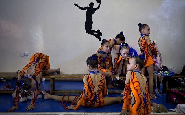 Gymnasts from Russian-speaking immigrant families warm up at a gymnastics competition organized for Israel's immigrant community, in the southern resort city of Eilat. Most of Israel's Olympic gymnasts are immigrants from the former Soviet Union. (photo credit: AP Photo/Oded Balilty)