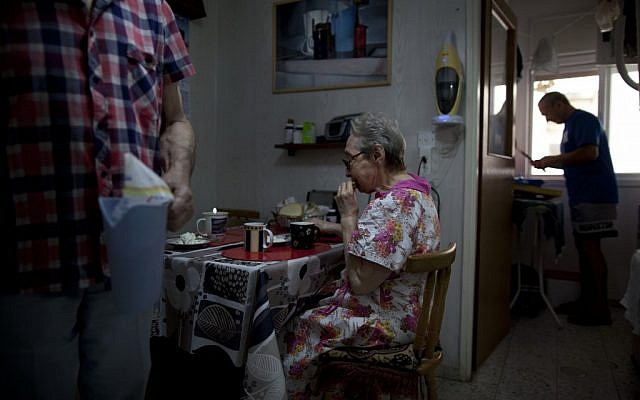 Bella Perlin, center, and Avraham Shapiro, left, Belarusian immigrants, eat breakfast in their home in Hadera, northern Israel. They emigrated to Israel in 1991 at the height of the wave of immigration from the former Soviet Union. (photo credit: AP Photo/Oded Balilty)