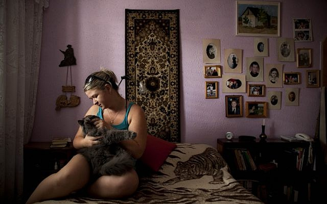 Alexandra Bahman, who emigrated to Israel from Moldova in 2006, sits in her bedroom with her cat. Bahman left Moldova with the carpet and photos that now decorate her bedroom walls, in Ashdod. (photo credit: AP Photo/Oded Balilty)