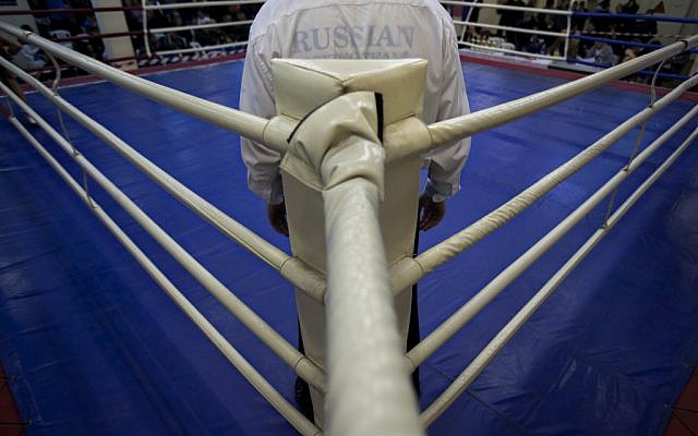 A Russian-speaking Israeli immigrant referee stands in the ring during a boxing competition for Israeli youth, in the southern Israeli town of Kiryat Gat. Many of Israel's boxing clubs are run by immigrants from the former Soviet Union (photo credit: AP Photo/Oded Balilty)