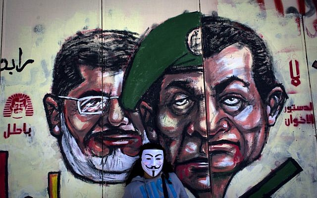 "A mural on the exterior wall of the presidential palace depicting President Mohammed Morsi, left, former military council ruler Hussein Tantawi, center, and ousted president Hosni Mubarak with Arabic that reads ""no, the brotherhood's constitution is not valid,"" in Cairo, Egypt, Dec. 8, 2012. (photo credit: Nasser Nasser/AP)"