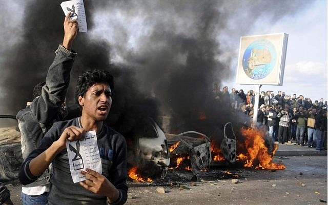 """Opponents of Egyptian President Mohammed Morsi hold pamphlets urging a """"no vote"""" on a constitutional referendum as cars burn during clashes between supporters and opponents of President Mohammed Morsi in Alexandria, Egypt, on on Friday, Dec. 14, 2012. (photo credit: AP)"""