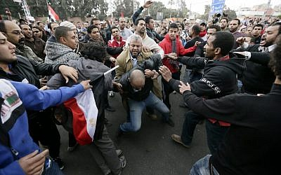 In this Wednesday, Dec. 5, 2012 file photo, Egyptian President Mohammed Morsi's supporters beat an opponent, center, during clashes outside the presidential palace, in Cairo, Egypt (photo credit: AP/Hassan Ammar)