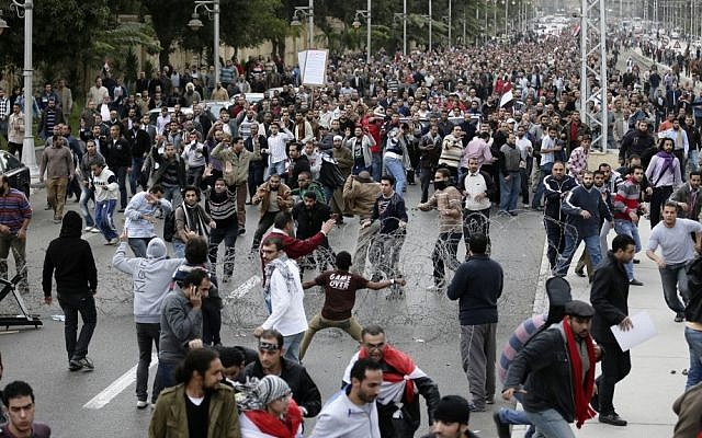 Supporters and opponents of Egyptian president Mohammed Morsi clash outside  the presidential palace in Cairo earlier this month (photo credit: AP/Hassan Ammar)