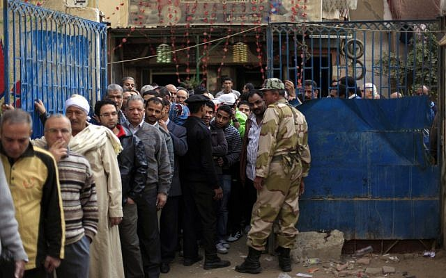 Soldiers watch as Egyptian men line up outside a polling station to cast their votes during a referendum on a disputed constitution drafted by Islamist supporters of President Mohammed Morsi in Cairo, Egypt, Saturday, Dec. 15, 2012. (photo credit: Khalil Hamra/AP)