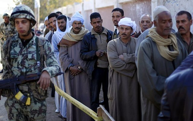 Egyptians line up outside a polling station wait their turn to cast their votes on Saturday, Dec. 22, 2012, during the second round of a referendum on a disputed constitution drafted by Islamist supporters of President Mohammed Morsi. in Fayoum, about 100 kilometers south of Cairo.(photo credit: Khalil Hamra/AP)