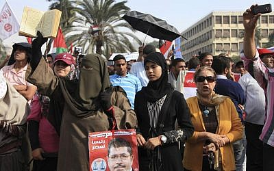 A supporter of Egyptian President Mohammed Morsi holds a Quran and a poster of the president at a rally in front of Cairo University on Saturday. (photo credit: AP/Thomas Hartwell)