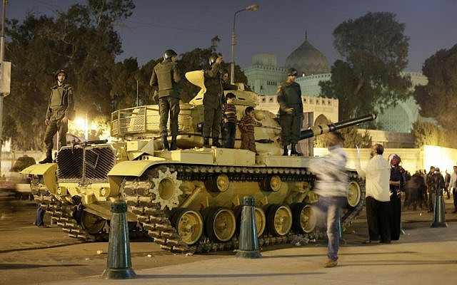 An Egyptian protester takes a picture with his mobile of his children on top of an Egyptian army tank outside the presidential palace in Cairo, Egypt, Saturday, Dec. 8, 2012 (photo credit: AP/Hassan Ammar)