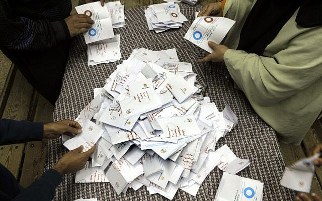 Egyptian referendum officials count votes at a polling station in Cairo, Saturday (photo credit: Amr Nabil/AP)