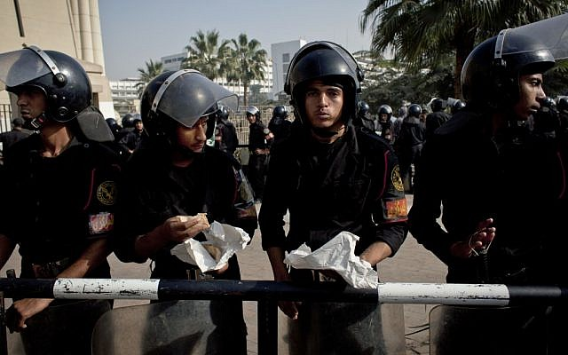 Riot policemen stand guard in front of Egypt's top court during a protest for supporters of Egyptian President Mohammed Morsi in Cairo on Monday, Dec. 3, 2012. (photo credit: Nasser Nasser/AP)