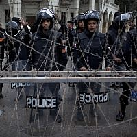 Illustrative image of Egyptian riot police standing guard behind barbed wire while protesters chant anti Muslim Brotherhood slogans, not pictured, during a demonstration in front of the presidential palace, in Cairo, Egypt, December 4 (photo credit: AP/Nasser Nasser)