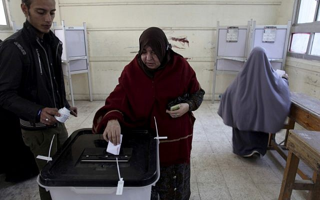 An Egyptian woman casts her vote during a referendum on a disputed constitution drafted by Islamist supporters of President Morsi in Cairo, Egypt, Saturday, Dec. 15, 2012. (photo credit: AP Photo/Khalil Hamra)