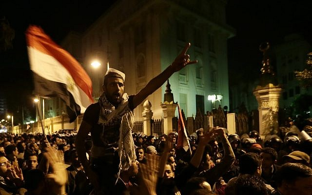 Egyptian protesters chant anti Muslim Brotherhood and Egyptian President Mohammed Mosri slogans outside the presidential palace after they broke a barbed wire barricade keeping them from getting closer to the presidential palace, in Cairo, Egypt, on Friday, December 7. (photo credit: AP/Hassan Ammar)