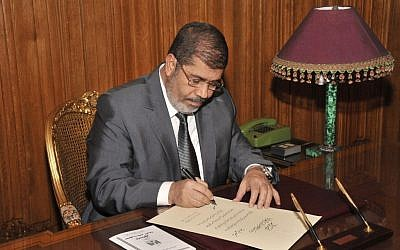 Then-Egyptian President Mohammed Morsi signs into law the country's Islamist-backed constitution in December 2012. (photo credit: AP/Egyptian Presidency)