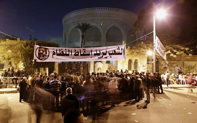 Egyptian protesters chant anti-Muslim Brotherhood and anti-Morsi slogans outside the presidential palace, under a banner with a  that reads 'the people want to bring down the regime,' in Cairo, Egypt on Saturday, December 8, 2012. (photo credit: AP Photo/Hassan Ammar)