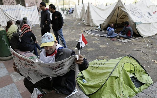 An Egyptian protester reads the newspaper as other sit next to their tents in Tahrir Square in Cairo, Egypt, Sunday, Dec. 9, 2012 (photo credit: AP/Hassan Ammar)