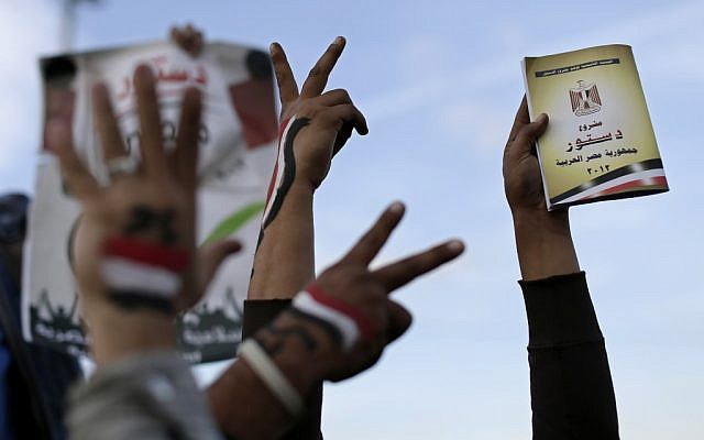 Supporters of President Mohammed Morsi with the Egyptian national flag painted on their hands, flash victory signs as one holds a copy of Egypt's draft constitution, right, during a demonstration, in Cairo, Egypt, Tuesday, Dec. 11, 2012. (photo credit: AP/Hassan Ammar)