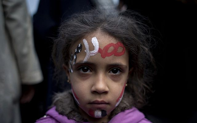 A girl with the colors of Egypt's national flag and Arabic text that reads 'Egypt, Morsi,' painted, at a demonstration in front of Egypt's top court in Cairo, Sunday, December 2, 2012 (photo credit: AP/Nasser Nasser)