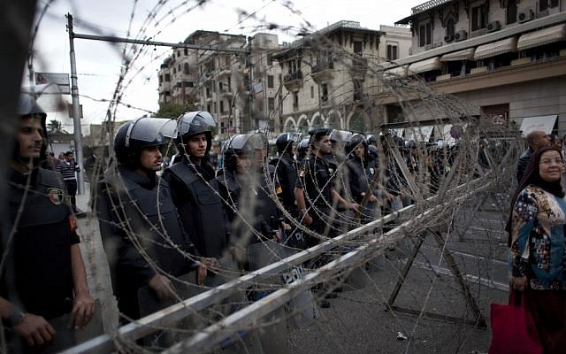 Egyptian riot police stand guard behind barbed wire, while protesters chant anti-Muslim Brotherhood slogans during a demonstration in front of the Presidential Palace, in Cairo, Egypt, Tuesday, December 4, 2012. (photo credit: AP/Nasser Nasser)