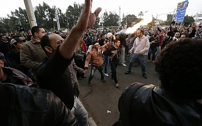 Egyptian President Mohammed Morsi's supporters and opponents clash outside the presidential palace, in Cairo, Egypt, Wednesday, Dec. 5, 2012 (photo credit: AP/Hassan Ammar)
