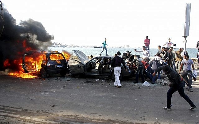 Cars burn during clashes between supporters and opponents of President Mohammed Morsi in Alexandria, Egypt, Friday, Dec. 14 (photo credit: AP/Ahmed Ramadan)