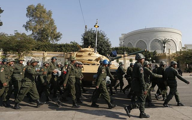 Egyptian soldiers walking past a military tank that secures the presidential palace in Cairo on December 13, 2012. (photo credit: Petr David Josek/AP)